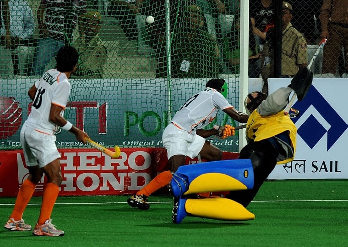 Indian hockey goalkeeper Adrian D'Souza (R) fails to stop a shot at goal during their World Cup 2010 match against England at the Major Dhyan Chand Stadium in New Delhi. (AFP Photo)