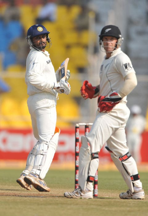 Harbhajan Singh plays a shot as New Zealand wicketkeeper Gareth Hopkins looks on during the last day of the first Test match between India and New Zealand in Ahmedabad. (AFP Photo)