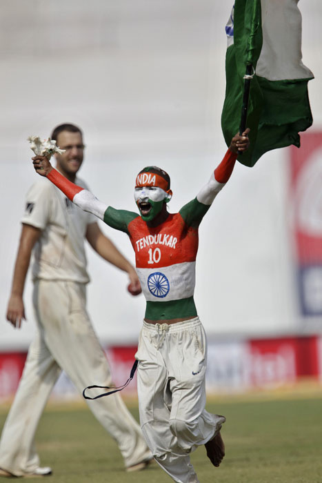 New Zealand's captain Daniel Vettori watches a fan who has his body painted with Indian tri-color run after greeting Harbhajan Singh during the last day of their first Test in Ahmedabad. (AP Photo)
