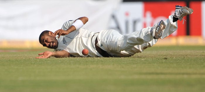 Jeetan Patel dives on the field to stop a ball during the fifth and final day of the first Test match between India and New Zealand in Ahmedabad. (AFP Photo)
