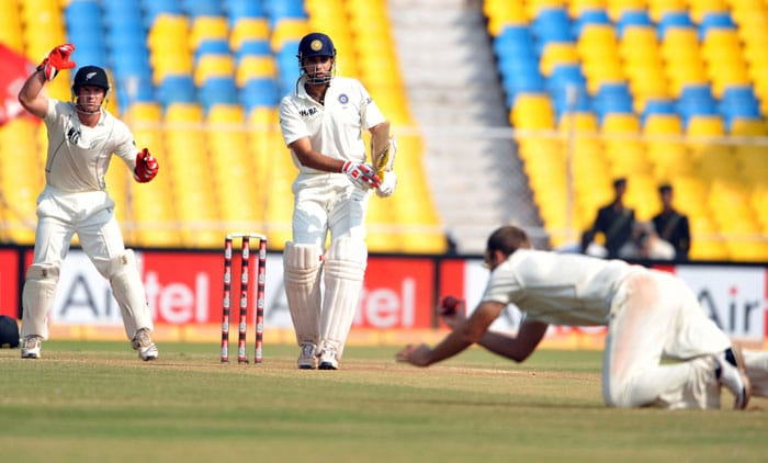VVS Laxman plays a shot as New Zealand team captain Daniel Vettori dives to stop the ball as wicketkeeper Gareth Hopkins looks during the last day of the first Test match between India and New Zealand in Ahmedabad. (AFP Photo)