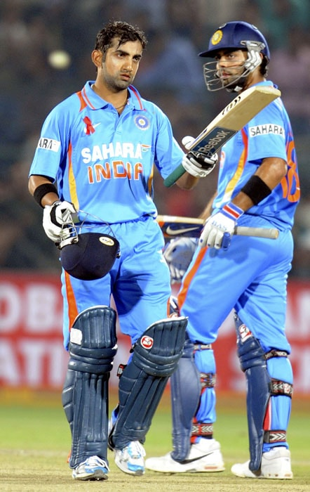 Gautam Gambhir waves to the crowd after completing a century (100 runs) during the second ODI between India and New Zealand at the Sawai Mansingh Stadium in Jaipur. (AFP Photo)