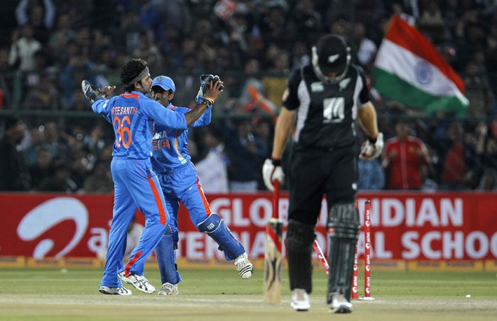 Daniel Vettori leaves after being bowled by S Sreesanth who celebrates with teammate Wriddhiman Saha during the second ODI in Jaipur. (AP Photo)