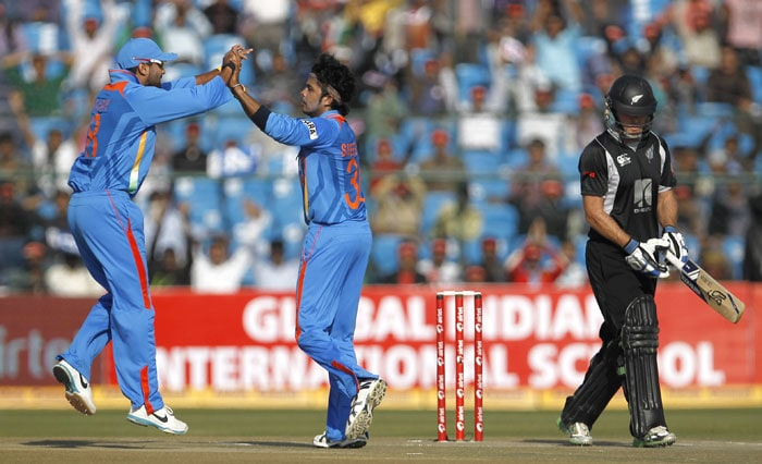 Jamie How leaves the field as Sreesanth celebrates with teammate Murali Vijay after claiming How's wicket during the second ODI in Jaipur. (AP Photo)