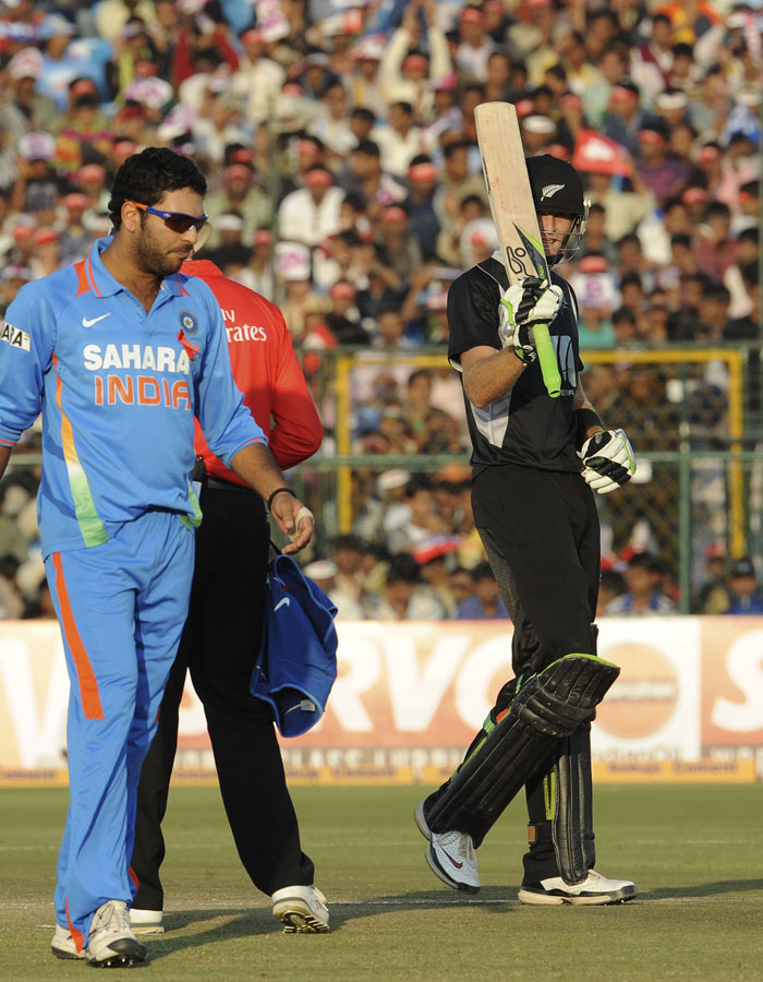 Martin Guptill gestures with his bat after his half-century (50 runs) as Yuvraj Singh looks on during the second ODI between India and New Zealand at the Sawai Mansingh Stadium in Jaipur. (AFP Photo)