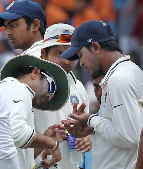 Sachin Tendulkar examines an injured finger of Pragyan Ojha during a drinks break on the fourth day of the third and final Test against New Zealand at the VCA Stadium in Nagpur. (PTI Photo)