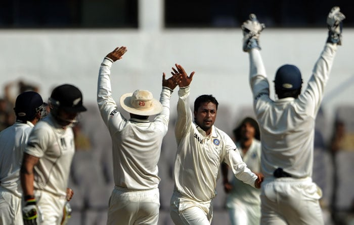 Pragyan Ojha celebrates with teammates after taking the wicket of Brendon McCullum on the fourth day of the third and final Test at the Vidarbha Cricket Association Stadium in Nagpur. (AFP Photo)