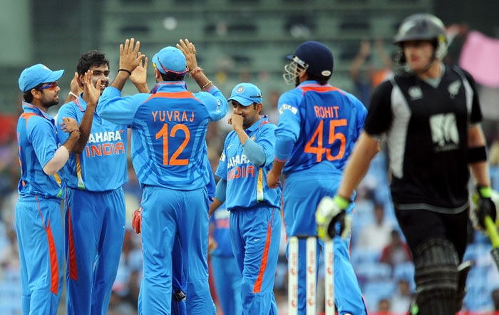 Indian cricketers congratulate Ravichandran Ashwin for taking the wicket of Scott Styris during the final ODI between India and New Zealand in Chennai. (AFP Photo)