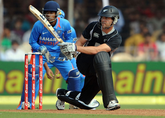 Wriddhiman Saha looks on as James Franklin plays a shot during the third ODI between India and New Zealand at the Reliance stadium in Vadodara. (AFP Photo)