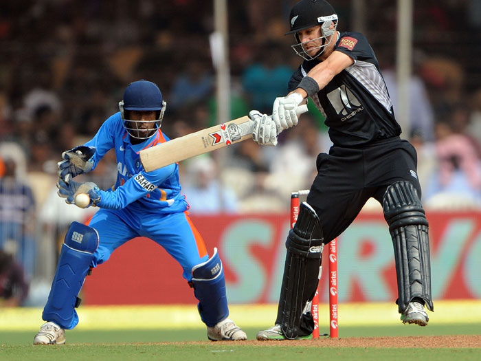 Wriddhiman Saha looks on as Nathan McCullum plays a shot during the third ODI between India and New Zealand at the Reliance stadium in Vadodara. (AFP Photo)