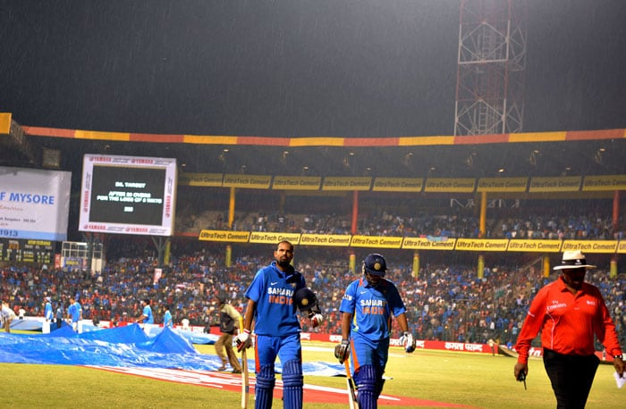 Yusuf Pathan and Saurabh Tiwary walk off the grounds as rain stopped play during the fourth ODI between India and New Zealand in Bangalore. (AFP Photo)