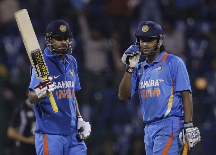 Yusuf Pathan raises his bat to celebrate scoring a half-century as teammate Saurabh Tiwary looks on during the fourth ODI between India and New Zealand in Bangalore. (AP Photo)