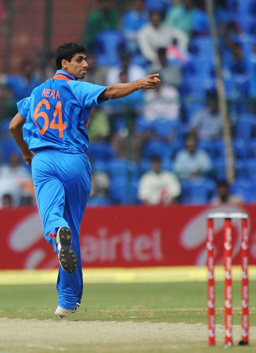 Ashish Nehra celebrates after taking the wicket of Jamie How during the fourth One-Day International match between India and New Zealand in Bangalore. (AFP Photo)