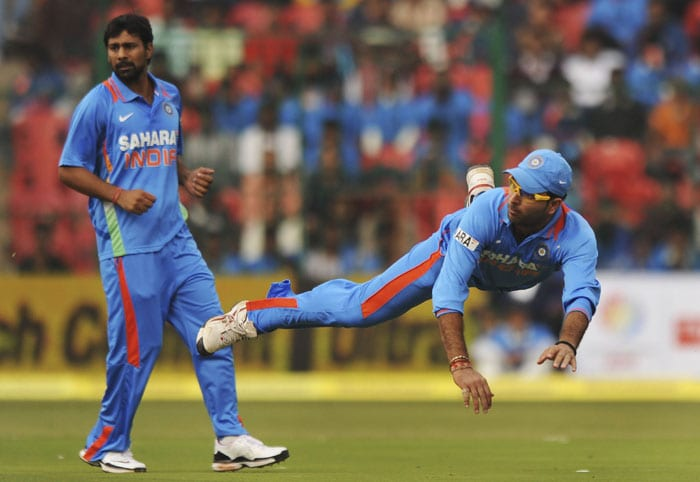 Yuvraj Singh jumps in the air after throwing the ball as teammate Praveen Kumar looks on during the fourth ODI match between India and New Zealand in Bangalore. (AFP Photo)