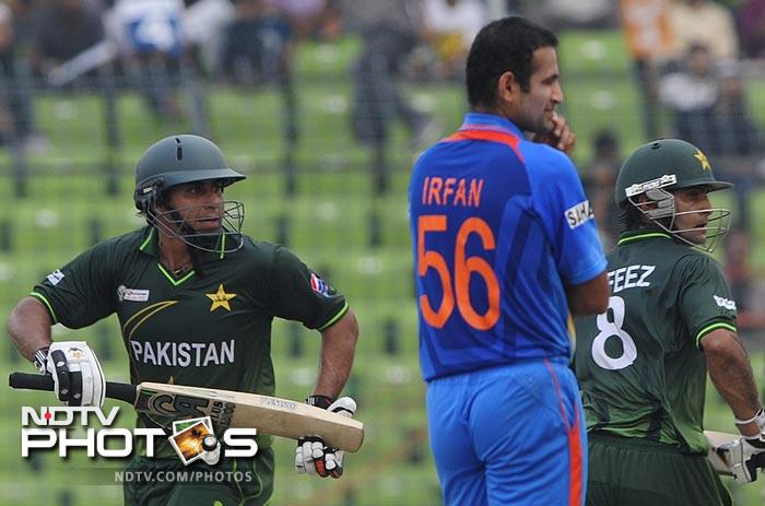 Nasir Jamshed and Mohammad Hafeez run between the wickets as Irfan Pathan looks on during the 5th ODI of the Asia Cup between India and Pakistan at the Sher-e-Bangla National Cricket Stadium in Dhaka. (AFP Photo)