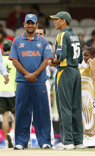 India captain Mahendra Singh Dhoni and Pakistan captain Younis Khan wait for the toss before the start of their Twenty20 World Championship warm-up match at the Oval in London. (AP Photo)