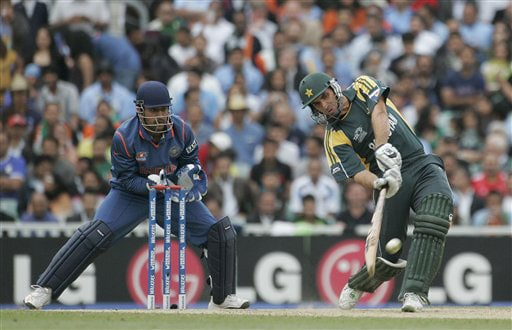 Misbah-ul-Haq hits out as Mahendra Singh Dhoni looks on in their warm up match for the Twenty20 World Championship at the Oval in London. (AP Photo)