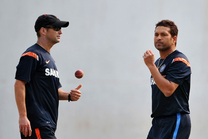 India's coach Gary Kirsten spins the ball as Sachin Tendulkar gets ready to bowl during a practice session in Nagpur. (AFP Photo)