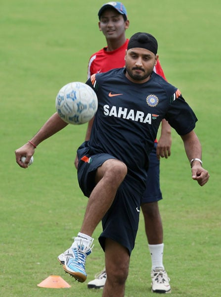 Harbhajan Singh plays with a football as a net player looks on during a practice session at MAC Stadium in Chennai. (PTI Photo)