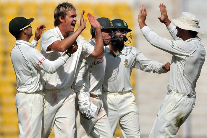 Graeme Smith celebrates with teammates the wicket of Mahendra Singh Dhoni on the third day of the first Test match between India and South Africa in Nagpur. (AFP Photo)