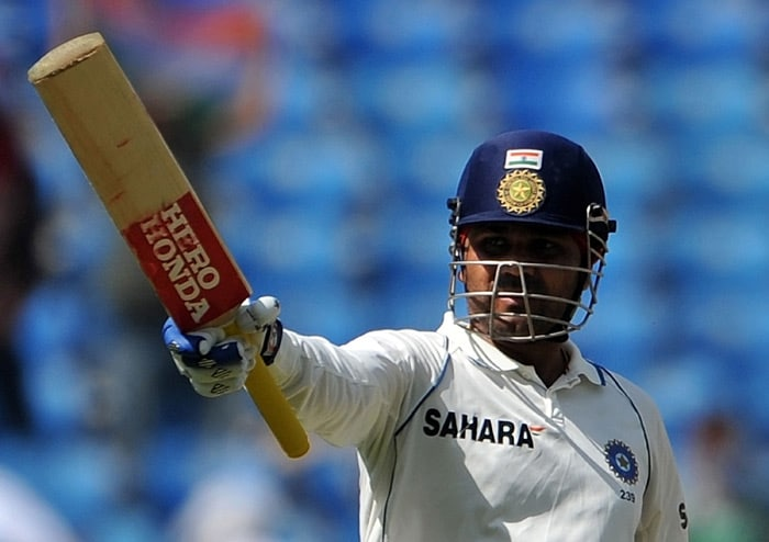 Virender Sehwag raises his bat after hitting a century on the third day of the first Test match between India and South Africa in Nagpur. (AFP Photo)