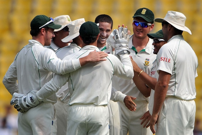 Wayne Parnell celebrates with teammates after taking the wicket of Subramaniam Badrinath on the fourth day of the first Test match between India and South Africa in Nagpur. (AFP Photo)