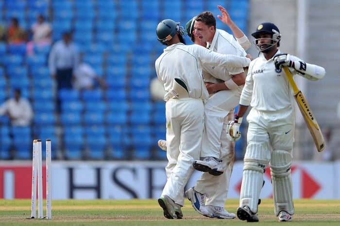 Dale Steyn is hugged by teammates AB de Villiers and Hashim Amla as Amit Mishra walks past after the South Africans beat India in the first Test of the two-match series in Nagpur. (AFP Photo)