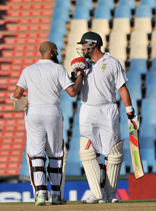 Jacques Kallis congratulates teammate Hashim Amla for making a century during the second day of the first Test against India at SuperSport Park in Centurion. (AFP Photo)