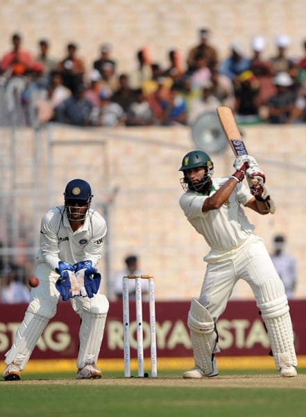 Hashim Amla plays a shot as Mahendra Singh Dhoni looks on during the final day of the second Test between India and South Africa at the Eden Gardens Stadium in Kolkata. (AFP Photo)