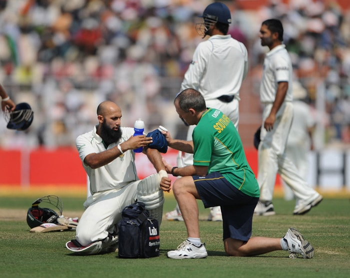 A South African team physiotherapist treats Hashim Amla who was hit by a ball during the final day of the second Test match between India and South Africa at the Eden Gardens Stadium in Kolkata. (AFP Photo)