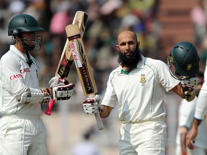 Hashim Amla (right) is watched by teammate Wayne Parnell as he raises his bat in celebration after scoring a century (100 runs) during the final day of the second Test match between India and South Africa at The Eden Gardens Cricket Stadium in Kolkata. (AFP Photo)