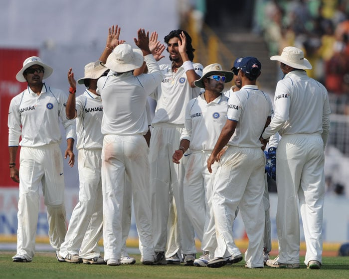 Indian cricketers congratulate team mate Ishant Sharma (centre) for the dismissal of Wayne Parnell during the final day of the second Test match between India and South Africa at The Eden Gardens Stadium. (AFP Photo)