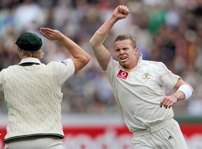 Australian bowler Peter Siddle celebrates with teammate Shane Watson after dismissing England batsman Andrew Strauss on the second day of the fourth Ashes cricket Test match in Melbourne. (AFP Photo)