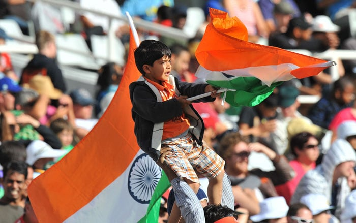 A young Indian fan holds up a national flag as he attends the first day of the third Test between India and South Africa at the Newlands Stadium in Cape Town. (AFP Photo)