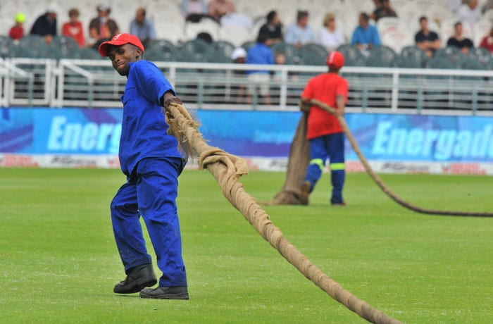 South African workers dry the cricket pitch on the first day of the third Test between South Africa and India at the Newlands Stadium in Cape Town. (AFP Photo)