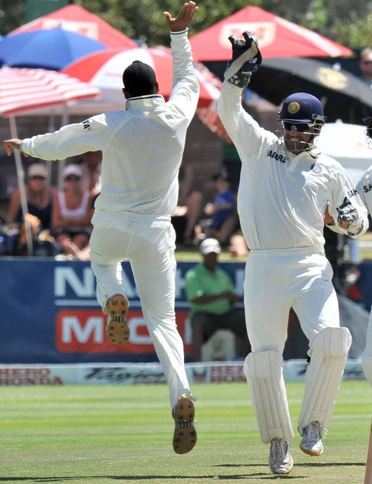 Mahendra Singh Dhoni and Harbhajan Singh celebrate the dismissal of Hashim Amla during the fourth day of the third Test between India and South Africa at the Newlands Stadium in Cape Town. (AFP Photo)