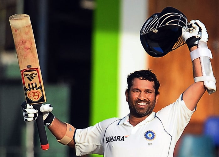 Indian cricketer Sachin Tendulkar raises his bat and helmet in celebration after scoring a century (100 runs) during the third day of the second Test match between Sri Lanka and India at The Sinhalese Sports Club Ground in Colombo on July 28, 2010. (AFP Photo)