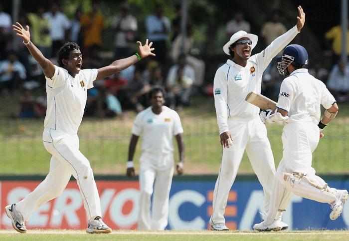 Ajantha Mendis (L) celebrates with teammate captain Kumar Sangakkara (2 R) after the dismissal of unseen Indian cricketer VVS Laxman during the third day of the second Test match between Sri Lanka and India at The Sinhalese Sports Club Ground. (AFP Photo)