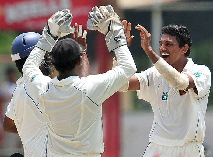 Sri Lankan cricketer Suraj Randiv (R) celebrates with his teammates after the dismissal of unseen Indian batsman Rahul Dravid during the third day of the second Test match between Sri Lanka and India at The Sinhalese Sports Club Ground. (AFP Photo)