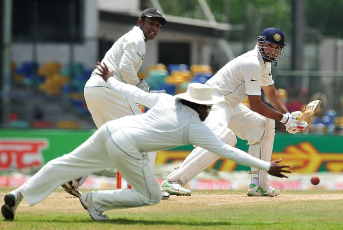 VVS Laxman plays a stroke (R) is watched by Sri Lankan wicketkeeper Prasanna Jayawardene (L) as teammate Mahela Jayawardene (C) dives in an attempt to field a ball during the third day of the second Test match between Sri Lanka and India at The Sinhalese Sports Club Ground. (AFP Photo)
