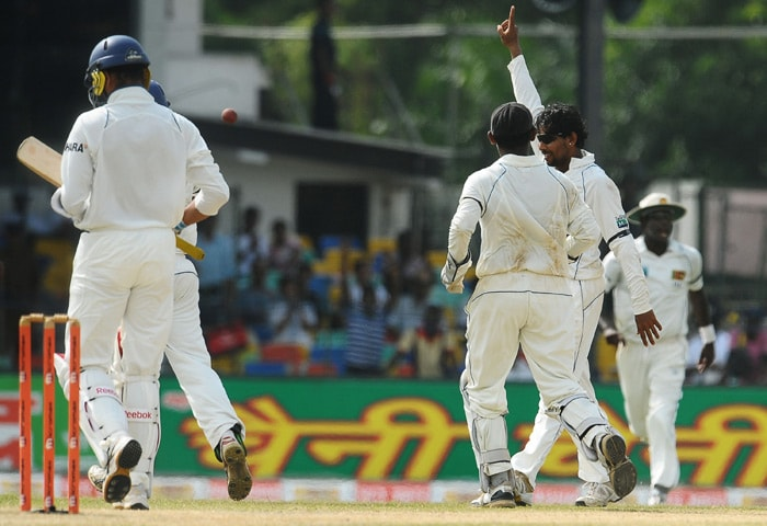 Sri Lankan cricketer Tillekeratne Dilshan (2 R) celebrates with wicketkeeper Prasanna Jayawardene (2 L) after the dismissal of Indian cricketer Harbhajan Singh (L) during the fourth day of the second Test match between Sri Lanka and India at The Sinhalese Sports Club Ground in Colombo on July 29, 2010. (AFP Photo)