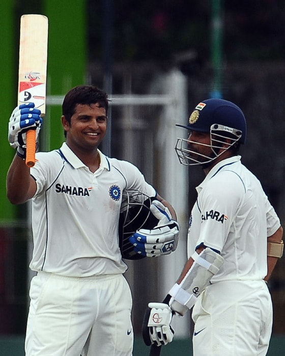 Indian cricketer Suresh Raina raises his bat to celebrate scoring a century (100 runs) as teammate Sachin Tendulkar (R) looks on during the fourth day of the second Test match between Sri Lanka and India at The Sinhalese Sports Club Ground in Colombo on July 29, 2010. Raina, 23, who was drafted in for his first Test cap July 28, reached a century in the second day of his debut performance. (AFP Photo)