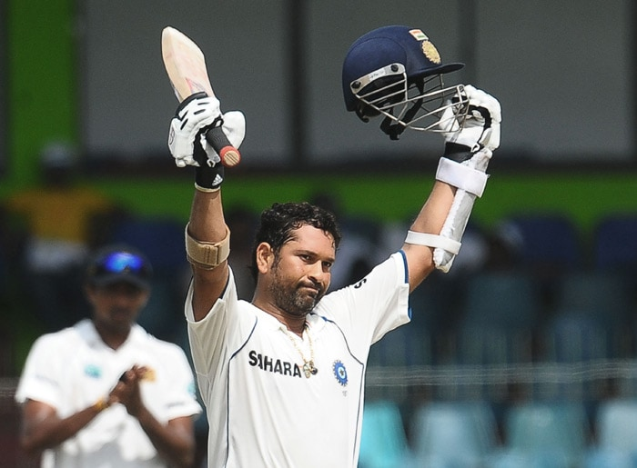 Indian cricketer Sachin Tendulkar raises his bat and helmet as he is applauded by the crowd for completing a double century (200 runs) during the fourth day of the second Test match between Sri Lanka and India at The Sinhalese Sports Club Ground in Colombo on July 29, 2010. (AFP Photo)