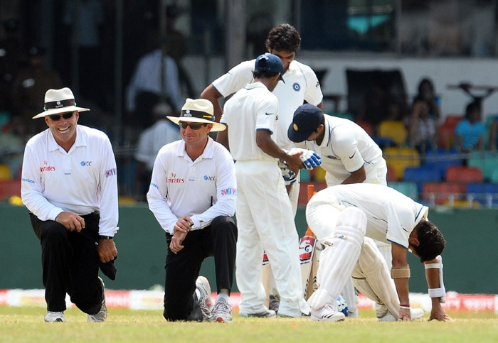Australian umpires Daryl Harper (L) and Rodney Tucker (2 L) look on as cricketers stretch and talk in the background during a break on the fourth day of the second Test match between Sri Lanka and India at The Sinhalese Sports Club Ground in Colombo on July 29, 2010. (AFP Photo)