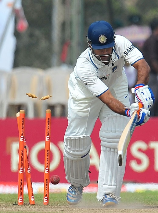 Indian cricket captain Mahendra Singh Dhoni is bowled by Sri Lankan bowler Lasith Malinga during the fifth day of the first Test match between Sri Lanka and India at The Galle International Cricket Stadium. (AFP Photo)