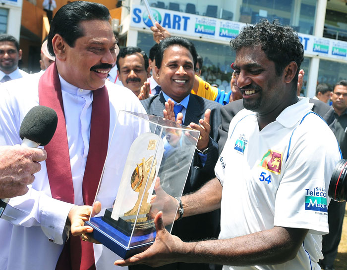Sri Lankan President Mahinda Rajapaksa (L) presents a memento to cricketer Muttiah Muralitharan (R) during the fifth day of the first Test match between Sri Lanka and India at The Galle International Cricket Stadium in Galle. (AFP Photo)
