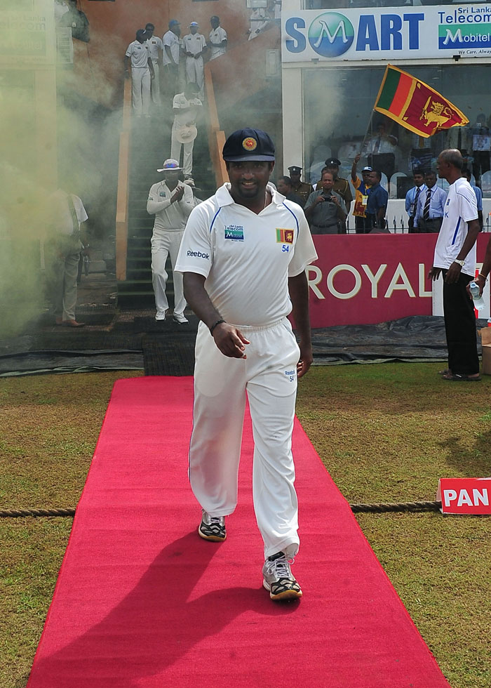 Sri Lankan cricketer Muttiah Muralitharan walks on a red carpet as he enters the field for the last day of his Test match career during the fifth day of the first Test match between Sri Lanka and India at The Galle International Cricket Stadium in Galle. (AFP Photo)