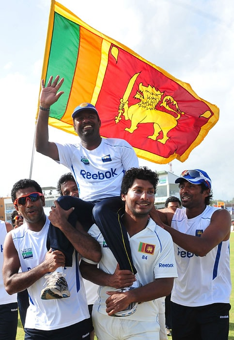 Sri Lankan cricketer Muttiah Muralitharan waves to the crowd as his teammates captain Kumar Sangakkara (2 R) and Damika Prasad (L) carry him around the pitch in a lap of honour after they won the first Test match between Sri Lanka and India at The Galle International Cricket Stadium. (AFP Photo)