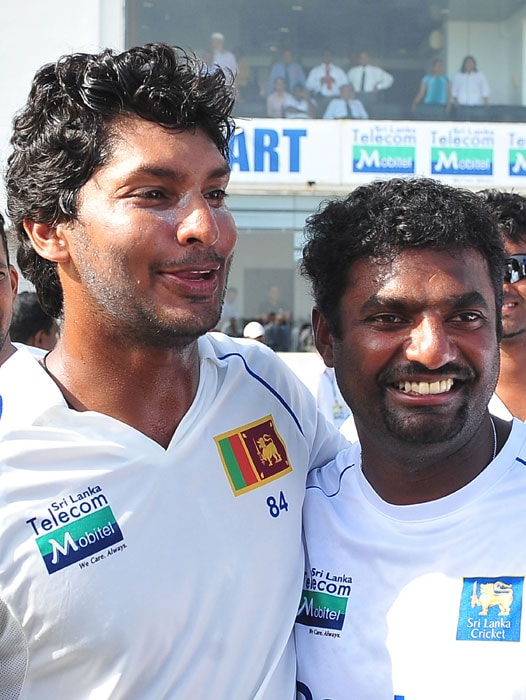 Sri Lankan cricketer Muttiah Muralitharan (R) poses for a photo with captain Kumar Sangakkara (L) after they won the first Test match between Sri Lanka and India at The Galle International Cricket Stadium. World bowling record-holder Muttiah Muralitharan retired with 800 Test wickets on Thursday as Sri Lanka thumped India by 10 wickets in their first match. (AFP Photo)