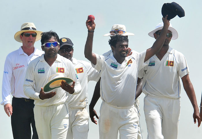 Sri Lankan cricketer Muttiah Muralitharan (2R) holds up the cricket ball as he walks back to the pavilion with teammates at the end of India's second innings during the fifth and final day of the first cricket Test match between Sri Lanka and India at The Galle International Cricket Stadium. Retiring world bowling record holder Muttiah Muralitharan of Sri Lanka reached the 800-wicket mark with his last delivery in Test cricket. The off-spinner, 38, had last man Pragyan Ojha caught at slip by Mahela Jayawardene to terminate India's second innings after lunch on the final day of the first Test at the Galle International Stadium. India, who were made to follow on 244 runs behind, were all out for 338 in their second knock. (AFP Photo)